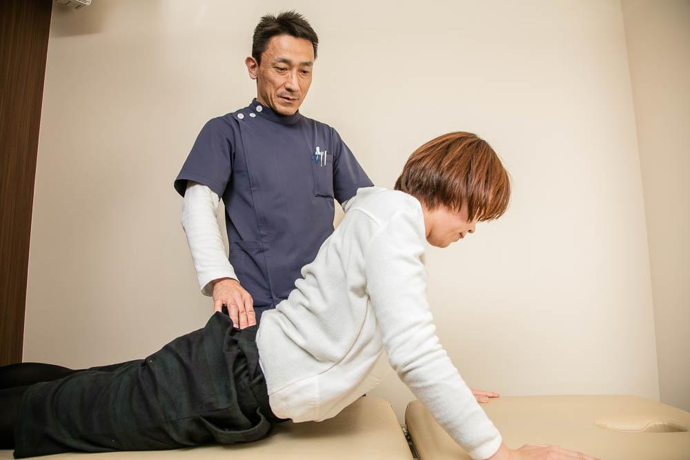腰椎を伸展させる指導をする様子
